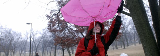 A gust of wind catches Cindy Scott's umbrella, flipping it upward, on her way home from class at Kansas University. Rain soaked Lawrence on Monday before turning to snow in the evening. Scott is a senior from Overland Park.