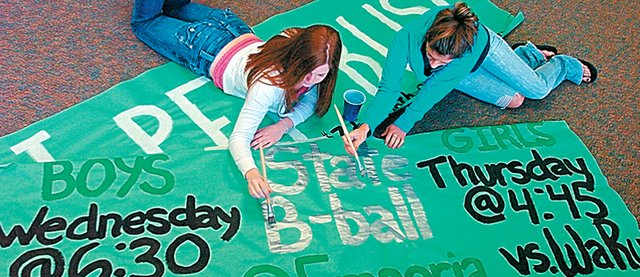 Free State High School students, from left, Abby Towner and Tori Hallenbeck, touch up a sign supporting the school basketball teams - both boys and girls teams advanced far into the state playoffs.