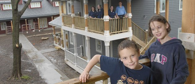 Joey Minder, 7, and his sister Sophia, 9, stand on the balcony of a house in the Delaware Street Commons in the 1200 block of Delaware. The Commons, which will be on the Spring Parade of Homes, is the only co-housing community of its kind in the region. In the background from left are Commons residents, from left, Vicki Penner, Linda Peckham, Jennifer Distlehorst and Penner's husband, Rich Minder. The neighborhood includes 21 energy-efficient condo-style homes and a communal house, pictured at lower left.