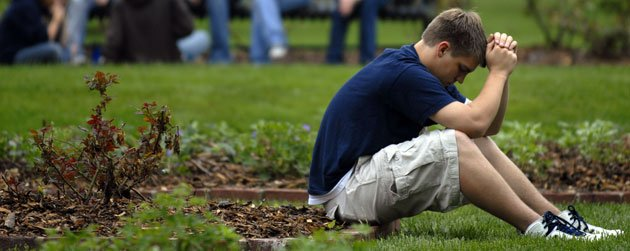 Veritas Christian School junior Stephen May has a quiet moment of prayer as others pray behind him during the National Day of Prayer at South Park. A group of about 100 people gathered Thursday at the park for the event.