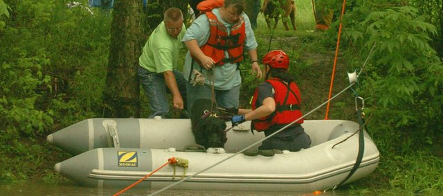 "Rescue teams from Douglas County and Osage County help Gail Jackson and her dog ""Rocket"" into a rescue boat at the FOB range near Lone Star Lake.  Rising water stranded six women and five dogs that were part of a Boxer rescue program which used the site as a retreat over the weekend."