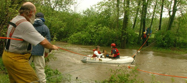 William VanDorn of the Overbrook Fire Department, left, pulls on a rope while Sandy Heard of Lawrence-Douglas County Fire & Medical helps Loretta Phillips and her dog Eco in a boat. Six women and five dogs were evacuated Monday from the Fraternal Order of Police lodge near Lone Star Lake because of rising creek levels. The women and dogs were attending a boxer rescue program at the lodge.