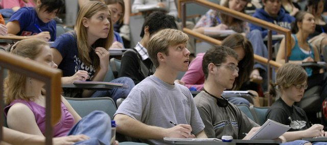 Kansas University freshman Isaac McPheeters, Lawrence, front and center, takes notes during a psychology lecture in Budig Hall. McPheeters, who was home schooled for most of his K-12 years, says the transition to college has gone well.