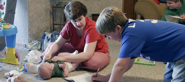 Luke Thomasson asks his mother, Donna, a question as she tends to her 5-month-old son, Chip. Donna Thomassons home schools her three boys - including Nick, at far right - in their house near Wellsville.