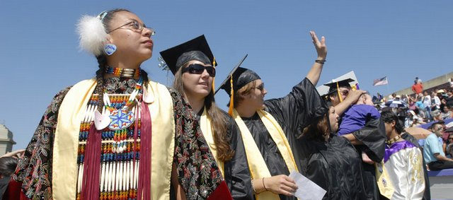Haskell Indian Nations University graduates, from left, Roberta Harjo, Katie Renwick and Jason Koontz form a line to receive their diplomas at Haskell's spring commencement. The university graduated 174 students Friday morning.