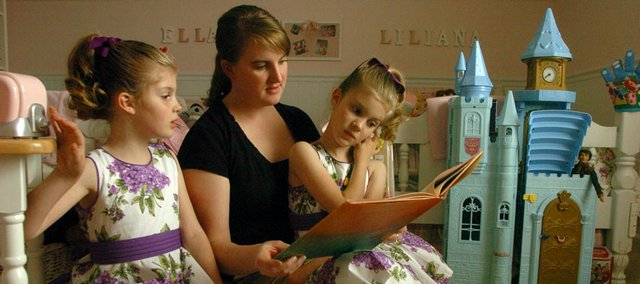 Tasha rose Keathley-Helms reads with daughters Liliana, left, and Ella in their west Lawrence home. The winner of the Journal-World Mother's Day essay contest's elementary division likes to read, draw and finger-paint with her daughters and son Jack, 3. Keathley-Helms also is pursuing a doctorate in political science at Kansas University.