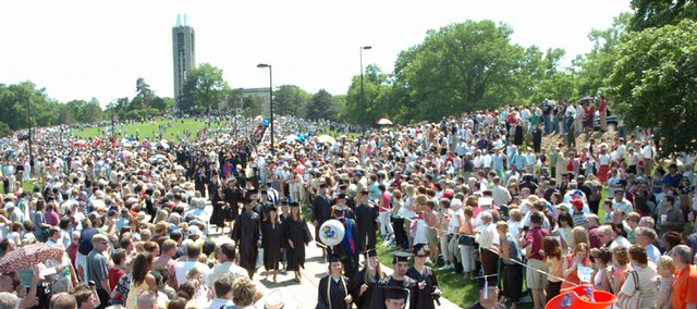 Thousands of Kansas University graduates walk down Campanile Hill during Sunday's commencement.