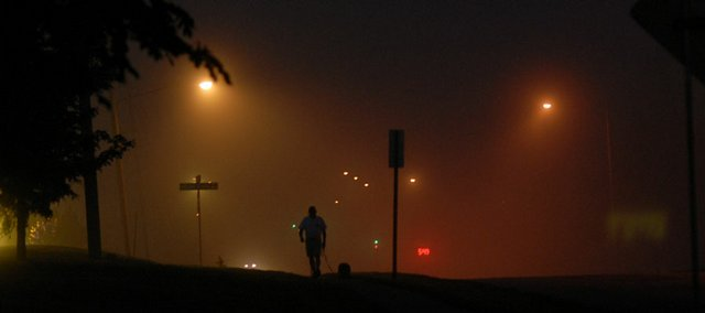 Chip Howat, walking his dog Izzy, passes through a 5:45 a.m. fog Thursday, May 10, along Wakarusa Drive.