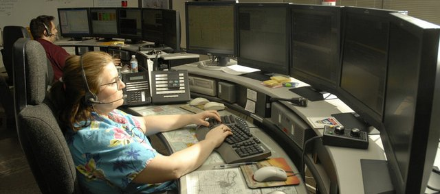 Douglas County Communications Officer Melinda Hegeman, right, has helped create an interactive Web story on the Douglas County emergency dispatch center.