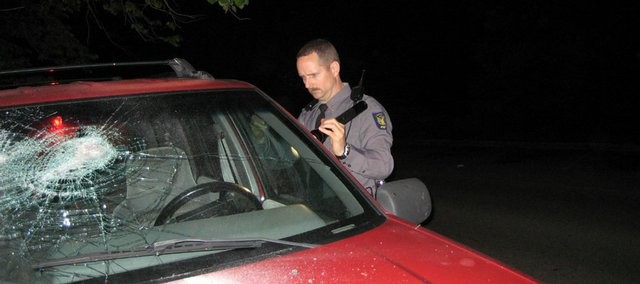 Lawrence police officer Michael McLaren inspects criminal damage to a vehicle near the Kansas University campus on May 10. Such crimes are not uncommon in Lawrence, particularly during the late night and early-morning hours.