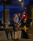 Dan Kozak, Topeka, plays his saxophone at the corner of Seventh and Massachusetts streets as the blue sky fades into night.