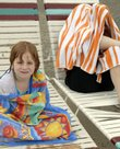 Bekah Keys, 6, left, takes a break to warm up while her mother, Lisa Keys, left, takes shelter under a towel during a light rain at Lawrence Outdoor Aquatic Center, 727 Ky. The pool opened Saturday and will remain open from 1 p.m. until 8:45 p.m. seven days a week for the rest of the season. Starting Tuesday, morning lap swimming will be available from 10 a.m. to 12:45 p.m. Monday through Friday through Aug. 24.
