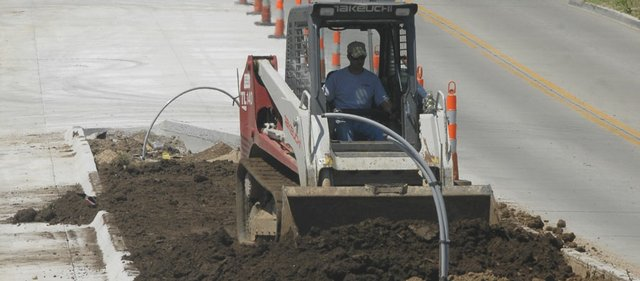Jeff Sauer, with R.D Johnson Excavating Co. of Lawrence, smooths dirt in the median on Kasold Drive between Bob Billings Parkway and 22nd Street in this file photo.  Construction crews will work throughout the summer on multiple roads in Lawrence.