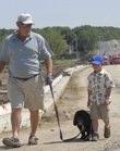 Marty Pattin, left, walks with his grandson Blaine Pattin, 6, and his dog Juju, along north Kasold Drive.
