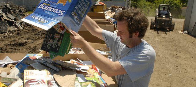 Andy Stowers unloads a box full of mixed paper at the Twelfth & Haskell Bargain Center, 1146 Haskell Ave.  Although some paid services provide Lawrence residents with the luxury of curbside recycling, many Lawrencians still hand deliver their recyclables.  The city of Topeka provides curbside recycling services to its residents.