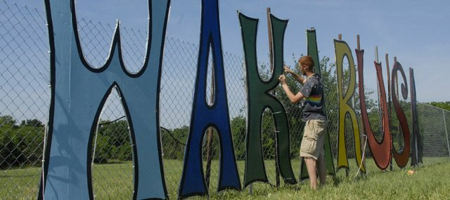 Gavin Carson, of Fayetteville, Arkansas, works on the Wakarusa sign. Crews were setting up for the Wakarusa Fest at Clinton Lake.