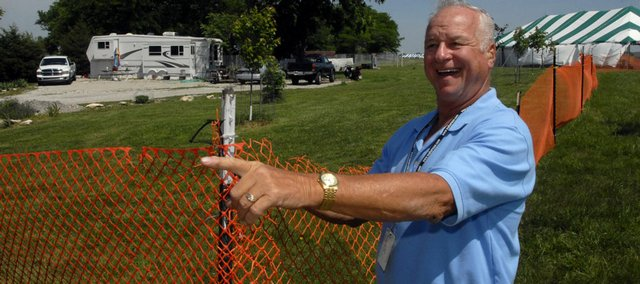 "Perry Buck, who Wakarusa festivalgoers have nicknamed ""Paparusa,"" greets some employees driving past his residence. Buck and his wife, Wanda, live in a trailer that has been situated permanently between the two largest stages at the annual music and camping event. An orange fence separates his property from the backstage and festival areas."