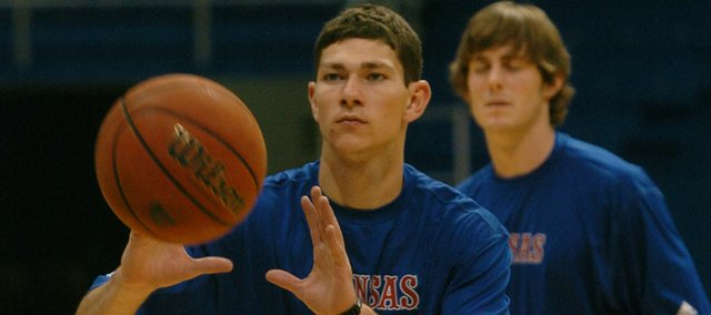 KU's Tyrel Reed, left, receives a pass before shooting a free throw as Conner Teahan looks on.