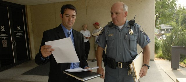 Hatem Chahine, left, an attorney representing local banks, talks with Sheriff's Department Sgt. Ken Fangohr at the home foreclosure auction on the steps of the Douglas County Judicial and Law Enforcement Center. The weekly auction was Thursday.