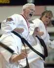 Lawrence resident Ginger Vermooten, front, a Tae Kwon Do black belt, front, warms up with her class as they practice kicking exercises Monday afternoon at ATA Black Belt and Leadership Academy, 5150 Clinton Parkway.