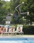 Erik Parrish, 12, does a flip-twist off the diving board at the Lawrence Aquatic Center. Parrish and his friends took turns on the diving board Tuesday under overcast skies and humid weather.