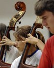 Lawrence High School junior Kati Wheatley, center, follows along with the bass section in a full orchestra rehearsal during the 2007 Kansas University Midwestern Music Camp Thursday afternoon at KU's Murphy Hall.