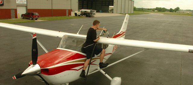 Andy Otto fuels a plane at the Lawrence Municipal Airport. A developer group's proposal for a business park near the airport is raising concerns that it could affect funding from the Federal Aviation Administration, which requires open space near runways.
