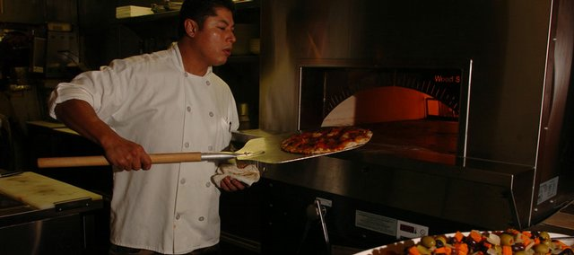 "Armando Paniagua checks on a pizza at Genovese, an Italian restaurant that opened last month at 941 Mass., in the former location of Mass. Street Deli. Paniagua, who worked for many years as a chef in California, now plays that role at Genovese, which he also co-owns. ""I love food,"" he says. ""I love making people happy."""