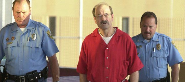 Convicted serial killer Dennis Rader, known as the BTK strangler, walks into the El Dorado Correctional Facility with two Sedgwick County sheriff's officers Aug. 19, 2005. Rader was convicted for killing 10 people in a 30-year span and sentenced to 10 consecutive life terms.