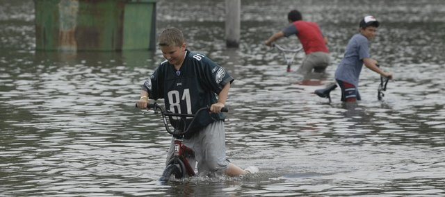 From left, Michael Pedersen, 13, Dylan Sauer, 13, and Sam Lee, 13, pedal through floodwater at Freedom Park in Ottawa.