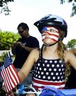 Helena All, 6, waits on her bike for the Old West Lawrence Independence Day parade to begin Wednesday at the intersection of Seventh and Ohio streets.