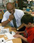 Harold Nelson, a counselor at Quail Run School, helps Alex Tomaszewski with an assignment while his class is at recess.