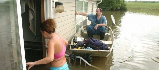 Osawatomie resident Krista Appleton, enters her trailer in southeast Osawatomie on the 4th of July hoping to salvage what she could, while Richard McCrackin  holds his boat next to the trailer. The water had been  over the roof of Appletons home for three days.