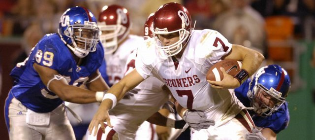 Kansas University's Nick Reig, right, and Charlton Keith converge on Oklahoma quarterback Rhett Bomar during last season's game at Arrowhead Stadium. Bomar, booted from the Sooners earlier this year for accepting an improper gift, is awaiting the NCAA's approval to play at his new home, Sam Houston State, a Division I-AA school in Huntsville, Texas.