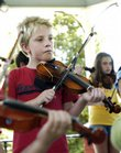 Three-year-old Mikhenna Brown, from left, Mark Smith, 8, and Hillary Podrebarac, 13, perform with other violin students Friday at South Park.