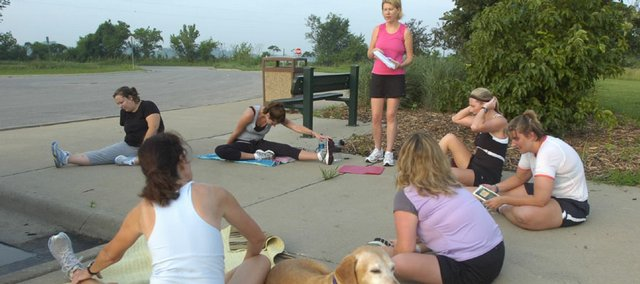 Participants in the EZ8 running camp stretch and cool down after a run on the South Lawrence Trafficway bike and hike path. Clockwise from foreground left are Coyla Lockhart and her dog, Laddie, Dyan Vespestad, Rachel Combs, coach Shannon Hodges, Erin Parmelee, Sandra Salem and Elinor Brown.