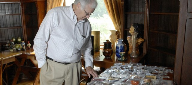 John Hughes, estate sales manager for the  Castle Tea Room, 1307 Mass., browses a collection of jewelry and coins at the historic Lawrence location.  The estate sale, scheduled for Thursday, Friday and Saturday from 8 a.m. to 5 p.m., features everything from antique tools, gold necklaces, coins, fur coats and steuben glass.  Highes organized items for the auction on Tuesday.