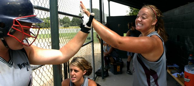 Lawrence Phenix pitcher Karen Spence slaps hands with teammate Laura Hunn as she enters the dugout after scoring Friday during bracket play of the AFA Nationals against the Missouri Sparks at Holcom Park. Center is Phenix player Jourdan Sumunja.