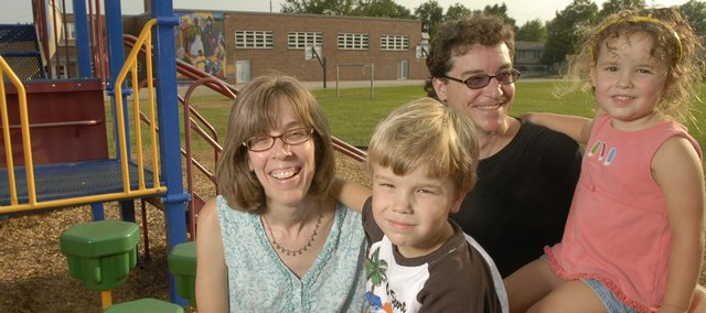 Ben Hoopes, 5, foreground right, will attend all-day kindergarten at Cordley this fall. Hoopes is joined by his parents Linda and Brad Hoopes and his sister Annelise, 3, on the Cordley school playground. Hoopes will be one of more than 300 students in Lawrence public schools involved in the return of all-day kindergarten to the district at Cordley and seven other schools.