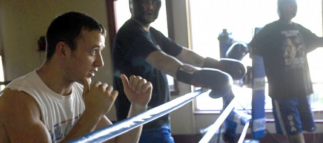Justin Montgomery, far left, discusses technique Friday at Walt's Boxing in North Lawrence. Walt's Boxing is open from 5 to 9 p.m., Monday through Friday and welcomes people of any skill level as well as those who just want to use the facility.