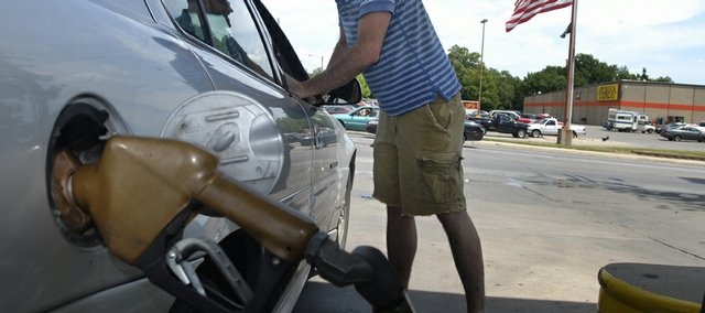 Kyle Griggs, of Lawrence, pumps gas while talking to his friend, Bione Dudley, of St. Louis, at the BP gas station at 23rd and Louisiana streets.