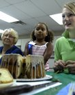 Fifteen-year-old Leslie Queen, right, listens as Karen Blakesee poses a question about her marble chiffon cake Monday at the Douglas County 4-H Fairgrounds. Taeghan Sharpe, 7, center, and Annette Larson, left, were assisting in the judging. Blakesee asked Queen what a chiffon cake has that a sponge cake doesn't; the answer is that chiffon cakes contain oil, while sponge cakes do not.