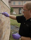 Daryl Ortgies, formulations chemist with Lawrence-based Prosoco Inc., applies a solvent that he helped develop to remove graffiti from the west wall of Corpus Christi Catholic Church, 6001 Bob Billings Parkway. Nine Lawrence churches have been damaged by graffiti since last weekend.