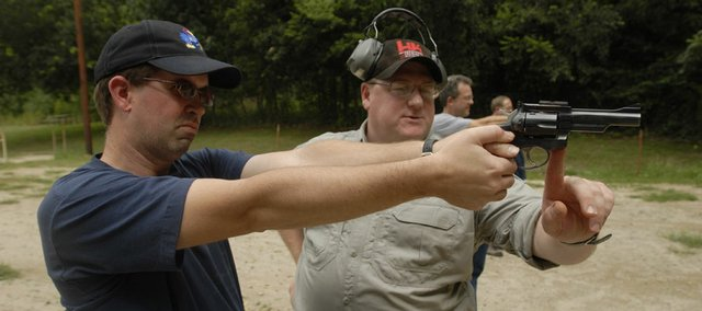 Journal-World Reporter Chad Lawhorn, left, receives instruction from Max Miller, a Lawrence police officer who also is a licensed firearms instructor, on Monday July 30, 2007 at the Fraternal Order of Police firing station near Lone Star Lake. An eight-hour training class is a prerequisite for carrying a concealed weapon in Kansas.
