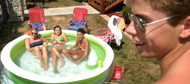 Andrew Winetroub, Kansas university senior from Leavenworth, introduces himself to three female KU students cooling off in a small pool outside their apartment on Tennessee Street. In the pool from left are Ginny Bauer, Wichita senior, Kristen Kuebelbeck, Overland Park senior, and Christine Pringle, Wichita senior. Winetroub and his friend Bailor Hardman, a KU senior from Osborne, stopped by to visit their new neighbors Tuesday. Temperatures are expected to be in the high 90s through the weekend before reaching 100 by Monday.