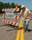 Doug Stephens, a road inspector for Douglas County, moves a sign across the road near the bridge over the Kansas River at Lecompton. The bridge linking Lecompton and Perry is set to reopen today after a five-month deck replacement project.