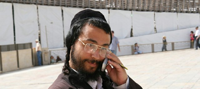 A Hasidic Jew talks on his cell phone outside the Western Wall - also known as the Wailing Wall - in Jerusalem. The wall is a remnant of the Second Jerusalem Temple, build around 70 A.D.