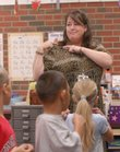 Kennedy School second-grade teacher Kay Becker leads her class in doing the Kennedy Pledge by sign language on the first day of school last week. Teachers are working under last year's contract until a new one between the school district and Lawrence Education Association is finalized.