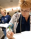 Lawrence Memorial Hospital nurse Yvonne Routte fills out paper work at a busy nurses' station in the emergency room.
