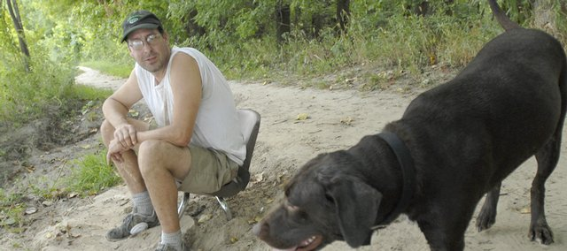 Kurt Nesbitt and his dog, Pocha, rest Thursday by the Kansas River near Burcham Park. Plans for a sculpture park near where Nesbitt was sitting have been put on hold after some people expressed concerns that it would damage wildlife habitat. Nesbitt, who is an artist and who has walked the river trail since he was 8, said he would support such a sculpture park.